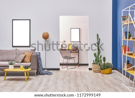 White blue wall concept living room style. Grey sofa and frame decoration. working table in the back and yellow bookshelf. #1172999149