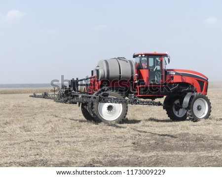 Kyiv region, Stepovoye, Ukraine - September 4, 2018: Exhibition of agricultural machinery. Agrotechnics works in the field. The tractor lights the field. Irrigation machine. #1173009229