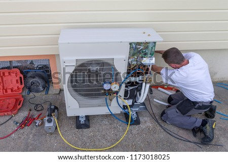 plumber at work installing a circulation heat pump Royalty-Free Stock Photo #1173018025