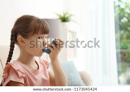 Little girl using asthma inhaler on blurred background Royalty-Free Stock Photo #1173045424