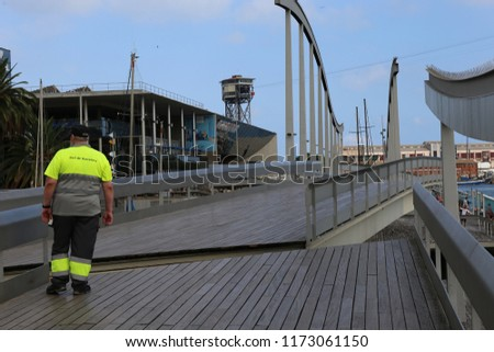 View of the end of La Rambla walking street, called 'La Rambla del Mar' which is a rotating bridge in Port Vell marina, Barcelona, Spain. August, 27, 2018. Scene of opening of the pedestrian walkway.  #1173061150