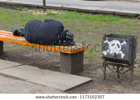 HomelessKYIV, UKRAINE - APRIL 16, 2018: Homeless man sleeps on a bench, head lies on shoes, closed up. The skull, as a sign of death, is painted on a trashcan man sleeps on a bench #1173102307
