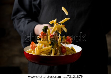 Cropped view of chef cooking Italian pasta with cheese, vegetabl #1173121879