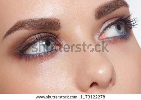 Close-up of female eyes with trendy evening make-up, thick even eyebrows and long rustnitsami. Gray-blue eyes, lenses, eyesight, cosmetology, make-up #1173122278