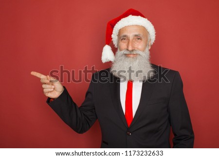 Closeup portrait of old man wearing red santa claus hat pointing with index finger to space at left, isolated on red background. Positive human emotion facial expression. #1173232633