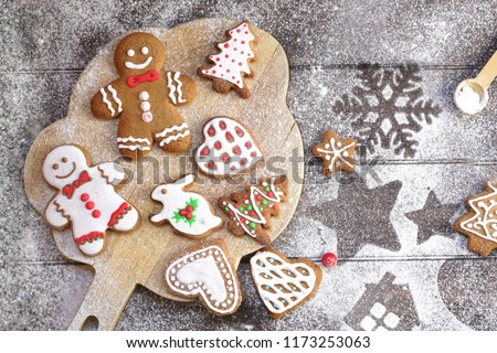 Christmas cookies of various shapes in sugar glaze on a cutting board on a brown wooden table sprinkled with flour, flat lay. Christmas composition with gingerbread men, fir-trees, rabbit #1173253063
