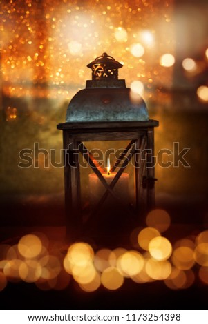 Burning lantern at christmas time in a cold winter night with golden bokeh