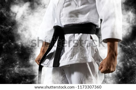 Guy poses in white kimono with black belt.  Japanese judo and sports concept #1173307360