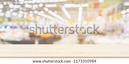 Wood table top with supermarket grocery store blurred defocused background with bokeh light for product display #1173310984