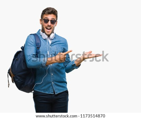 Young handsome tourist man wearing headphones and backpack over isolated background amazed and smiling to the camera while presenting with hand and pointing with finger. #1173514870