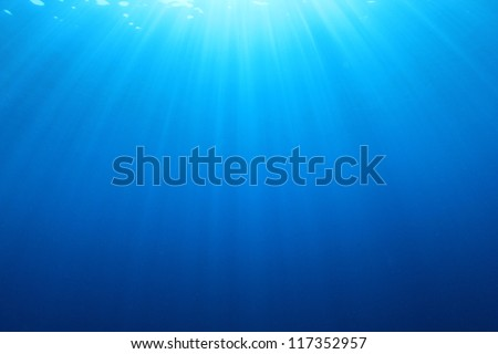 Blue water background sun rays