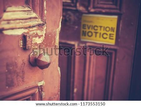 Grungy Old Door With A Yellow Eviction Notice #1173553150