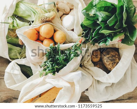 fresh vegetables in eco cotton bags on table in the kitchen. lettuce, corn, potatoes, apricots, bananas, rucola, mushrooms from market. zero waste shopping concept.   ban plastic #1173559525