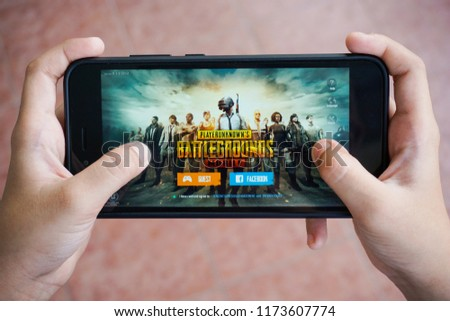 Kuala Lumpur, Malaysia - 7 September 2018: Hand holding a smartphone with Player's Unknown Battleground also known as PUBG online shooting gaming #1173607774
