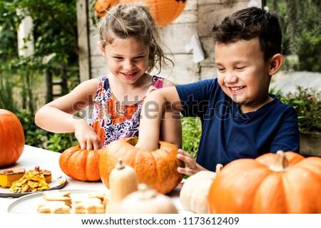 Young kids carving Halloween jack-o-lanterns Royalty-Free Stock Photo #1173612409
