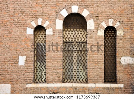 Ancient wall with three windows in Gothic style and stone fragments with Roman unreadable lettering. Lintel stone and brick. Brescia, Italy. #1173699367