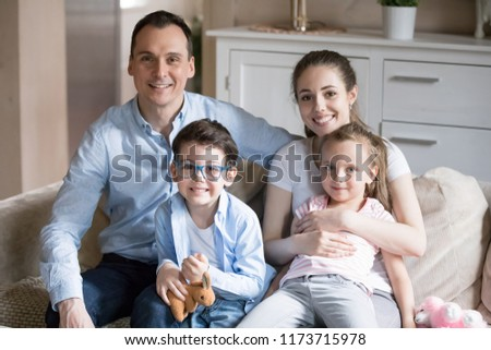 Portrait of happy family of four sit on couch in living room, smiling young parents hug small kids taking picture together, mom and dad embrace son and daughter when making photo for album in house #1173715978