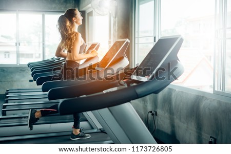Healthy People running on machine treadmill at fitness gym, Work out concept.Picture of people doing cardio training on treadmill in gym. #1173726805