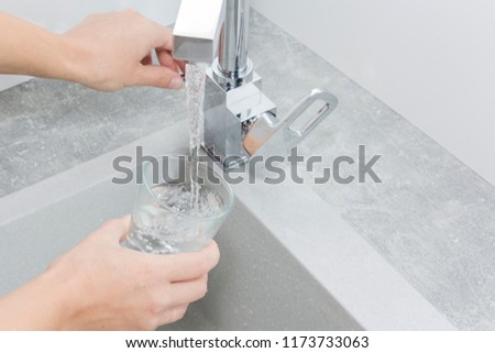 Hand holding a glass of water poured from the kitchen faucet. #1173733063