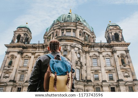 A tourist or traveler with a backpack looks at a tourist attraction in Berlin called Berliner Dom. Traveling in Germany. #1173743596
