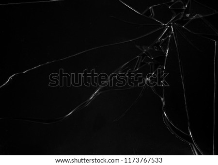 A broken glass, with multiple braks, on a black background. Many shattered pieces. Black-and-white texture (use overlay, multiply or screen mode).