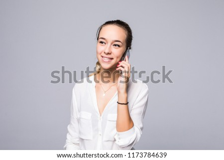 Cheerful young woman talking on mobile phone isolated on gray background #1173784639
