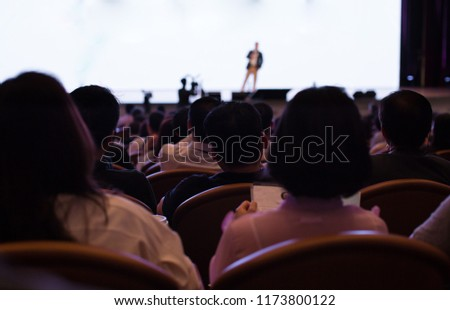 Men and Women Listen to Presenter on Stage with White Screen Background. Global Tech Management Corporate Meeting Event. Business Trainer Lecturing to Global Audience at International Summit. #1173800122