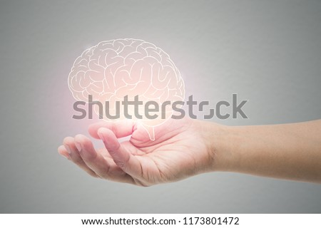 Man holding brain illustration against gray wall background. Concept with mental health protection and care. Royalty-Free Stock Photo #1173801472