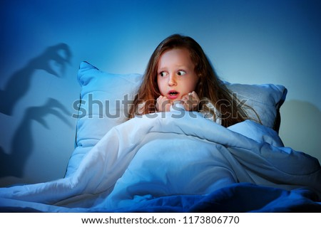 Sleepless girl in her bed having fears of night monsters Royalty-Free Stock Photo #1173806770