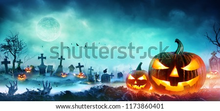 Jack O' Lanterns And Zombie Hands Rising Out Of A Graveyard In Misty Night  #1173860401