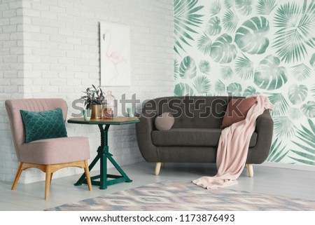 Table with flowers between pink chair and settee in apartment interior with poster and wallpaper. Real photo #1173876493
