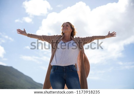 Happy mature woman with arms outstretched standing on the beach #1173918235
