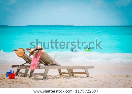family beach vacation- chairs and kids play at sea #1173922597