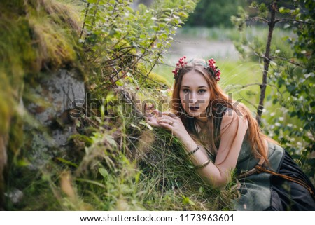 A forest witch. A beautiful girl lies on a moss in a beautiful wreath and a green dress. Moss on the ground. #1173963601