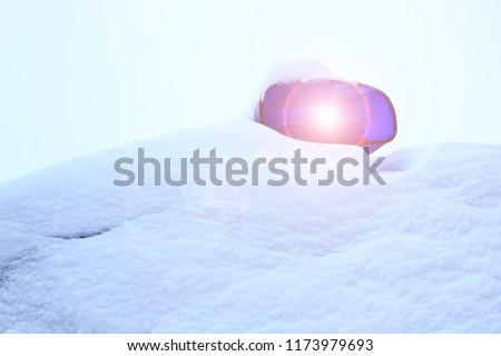 it's snowing outside. police car all in the snow. only flashing lights are visible.