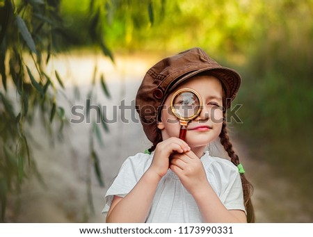 Little girl with magnifying. Little detective Royalty-Free Stock Photo #1173990331