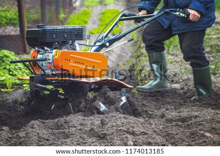 plowing the land in the garden with a cultivator. agricultural work on plowing the field for sowing seeds. a man plows the land with the help of motor cultivator. #1174013185