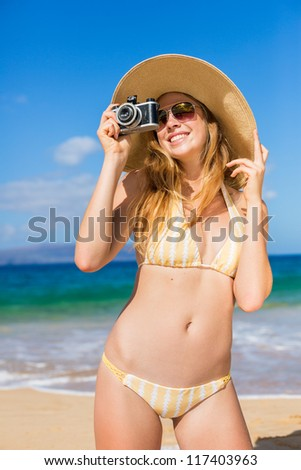 Beautiful Young Woman at the Beach with Vintage Camera #117403963