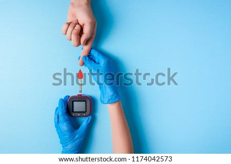 Nurse making a blood test. . Man's hand with red blood drop with Blood glucose test strip and Glucose meter. Copy space. Top view #1174042573