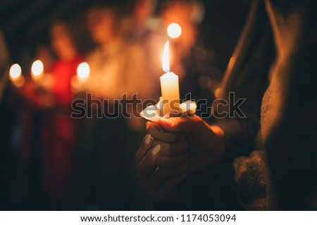 a girl holds a lighted candle in her hands, a religious tradition, a symbol of the Christian faith, a wax candle burns with an even flame, blow out a candle, a smoke from an extinguished wick  #1174053094