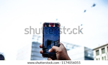 Putrajaya, Malaysia - 31 August 2018 : Close-up of male's hand taking video of helicopter during Merdeka Parade in Putrajaya #1174056055