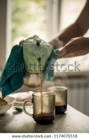 Coffee is poured from a geyser coffee machine into a glass #1174070518