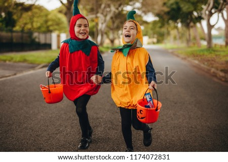 Happy kids in halloween costume trick or treating outdoors. Two little girls in halloween costume with buckets walking outdoors on the street. #1174072831