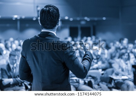 Speaker giving a talk on corporate business conference. Unrecognizable people in audience at conference hall. Business and Entrepreneurship event. Blue toned grayscale image. #1174144075