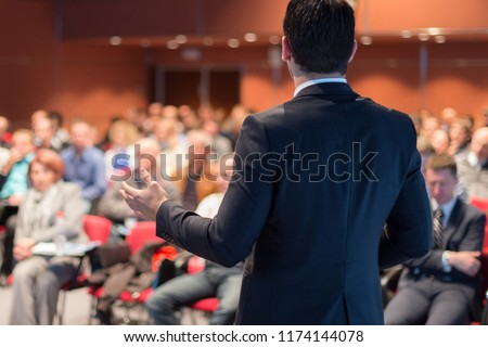 Speaker giving a talk on corporate business conference. Unrecognizable people in audience at conference hall. Business and Entrepreneurship event. #1174144078