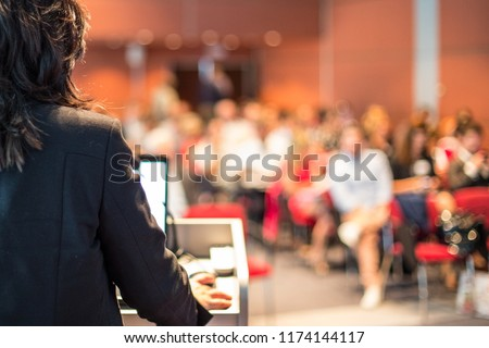 Female speaker giving a talk on corporate business conference. Unrecognizable people in audience at conference hall. Business and Entrepreneurship event. #1174144117