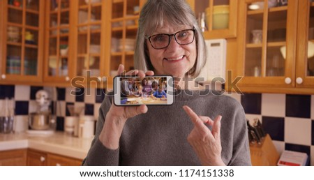 Happy white grandmother showing off video of family on mobile device in kitchen