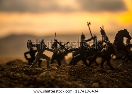 Medieval battle scene with cavalry and infantry. Silhouettes of figures as separate objects, fight between warriors on sunset foggy background. Selective focus #1174196434