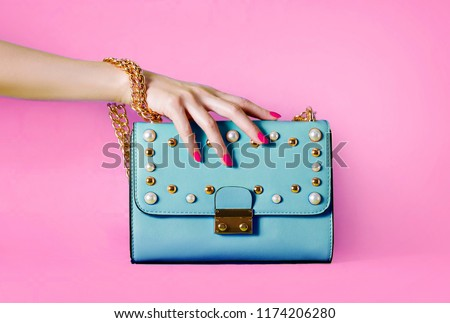 Sky blue handbag purse and beautiful woman hand with red manicure isolated on pink background. #1174206280