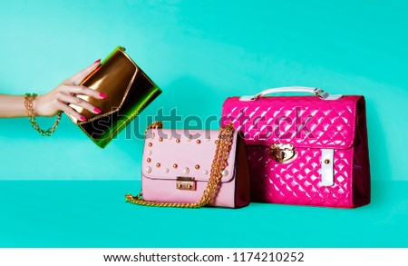 Group of beautiful purses bags and woman hand holding one handbag.  Shopping image. #1174210252